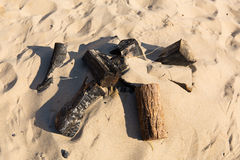 Remains of a small campfire with burned wood logs and sand on a beach. Remains of a small campfire with charred burned wood logs and sand on a beach in the sun Stock Photo