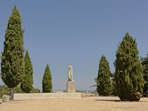 Remains of stone statue of emperor Trajan in between trees on trajano viewpoint in Italica stock photography