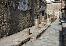 Remains of a street in Herculaneum Parco Archeologico di Ercolano. Pictured are remains of a street in Herculaneum in the Parco Archeologico di Ercolano. The Royalty Free Stock Photo