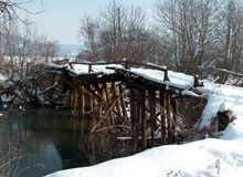Remains of a wooden bridge on the Mlava River under the snow. stock photos