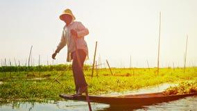 Remando uno stile tradizionale della barca, con la gamba, su un fondo di galleggiamento fa il giardinaggio stock footage