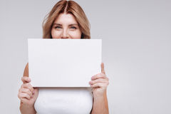 Remarkable bright woman hiding her smile. Feminine and strong. Positive hilarious adorable lady using a piece of paper covering up half of her face while posing stock photography