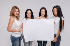 Remarkable powerful women sending a strong message. Call to action. Serious independent diverse ladies uniting for a cause while holding up a pig blank poster Stock Image