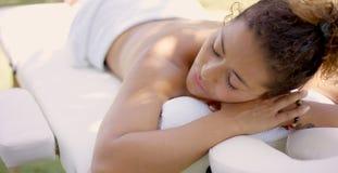 Remate abajo de la opinión la mujer en la tabla del masaje Imágenes de archivo libres de regalías