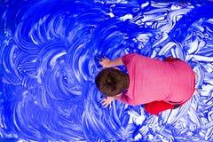 Remate abajo de la opinión sobre el muchacho que mancha las manos en pintura Fotos de archivo libres de regalías