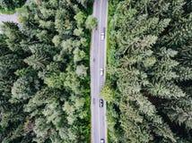 Remate abajo de la vista aérea de los coches que pasan cerca en el camino en un bosque Fotos de archivo libres de regalías