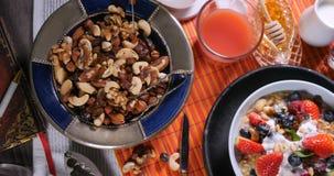 Remate abajo de la vista de cereales con las bayas, las frutas secas y la crema Imagen de archivo