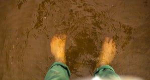 Remate abajo de la vista de los pies que se colocan en agua clara que fluye baja sobre la piedra arenisca rojiza Imagenes de archivo
