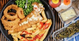 Remate abajo de la vista del los pescado frito con patatas fritas ingleses con los guisantes de jardín y las cebollas del anillo Imágenes de archivo libres de regalías