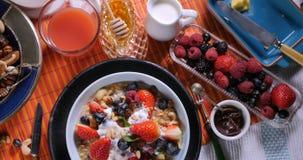 Remate abajo de vista de un desayuno de cereales con las bayas, las frutas secas y la leche Imagen de archivo