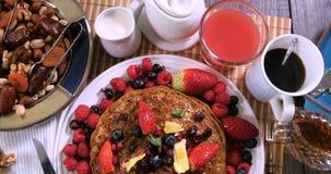 Remate abajo de vista de un desayuno de crepes con las bayas y las frutas secas almacen de metraje de vídeo