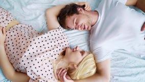 Remate abajo del giro sobre los pares románticos que mienten en la cama cara a cara por la mañana almacen de video