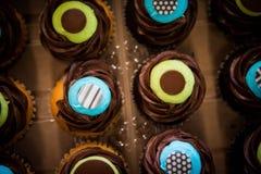 Remate abajo del tiro de las magdalenas azules y amarillas coloridas del chocolate Imagen de archivo libre de regalías