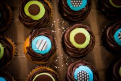 Remate abajo del tiro de las magdalenas azules y amarillas coloridas del chocolate Foto de archivo libre de regalías