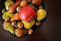 Remate la vida inmóvil de granadas, de manzanas, de peras y de nueces en un florero Imagen de archivo libre de regalías