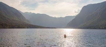Rematura della famiglia in crogiolo di canoa sul bello lago Bohinj, Slovenia Immagini Stock
