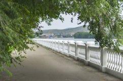 Remblai du fleuve Irtych vu par la voûte de couronne d'arbre avec les grues de quai, les résidences, les Chambres, et les montagn photo stock