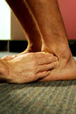Remedial Massage Ankle. Remedial massage therapist working on ankle, low angle of view Stock Image