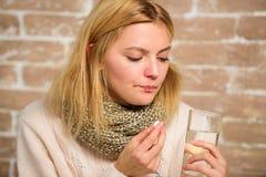 Remedios del dolor de cabeza y de la fiebre La mujer despeinó el agua de cristal del control de la bufanda del pelo y hace tablet imagenes de archivo