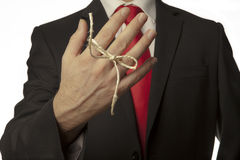 Remember. Man in buisness suit with a knot around his finger to make him remember something Stock Photo
