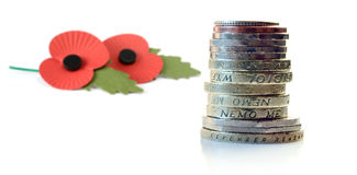Remember. Studio image of UK coins and remembrance poppies. Focus on the bottom coin - engraved with the words 'remember remember'. Copy space Stock Images