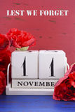 Remember, Armistice and Veterans Day Calendar. White block vintage calendar with large red Flanders poppies on red and blue wood background for Remembrance Royalty Free Stock Photo