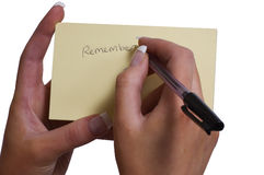 Remember. Female Hand writing Remember on Sticky note Royalty Free Stock Photography