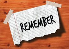 REMEMBER handwritten on torn notebook page crumpled paper on wood texture background. Illustration Stock Photos