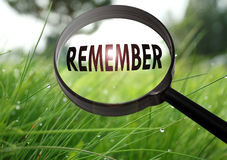 Remember. Magnifying glass with the word remember on grass background. Selective focus Stock Image