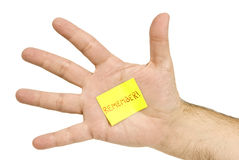 Remember!. A male hand with a yellow Post-it-Note stuck to it with the note: Remember! on it Stock Image