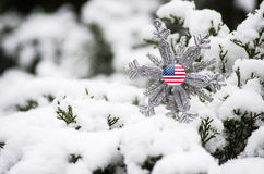 Remember Military Personnel. A Christmas ornament placed on a snow covered pine tree.  This is a symbol of remembering our military at Christmas that are away Royalty Free Stock Image