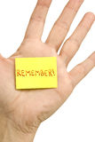 Remember Note. A male hand with a yellow post-it-note stuck to it with the note: Remember Stock Photography