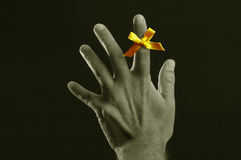 Remember our troops. Yellow bow in support of our troops on a male hand --selective toning Royalty Free Stock Photography