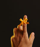 Remember our troops. Yellow bow in support of our troops on a male hand royalty free stock photo
