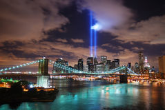 Remember September 11. New York City. Manhattan panorama view with Brooklyn Bridge at night with office building skyscrapers skyline illuminated over Hudson Royalty Free Stock Photography