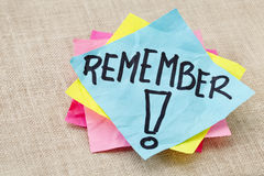Remember on sticky note. Reminder concept - remember word handwritten on blue sticky note Royalty Free Stock Photography