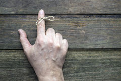 Remember. String on index finger of an elderly man. Wooden background Stock Images