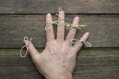 Remember. Twine in the fingers of an elder. Wooden background Stock Photos
