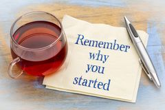 Remember why you started. Inspirational handwriting on a napkin with a cup of tea stock photography