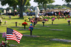 Remembrance. An American flag in the foreground with a funeral taking pace in the distant background stock photography