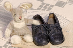 Remembrance of Childhood Concept: Vintage Toy Bunny and Children`s Shoes. Childhood concept with an old toy bunny and a pair of retro worn-out children`s shoes Stock Photo
