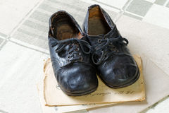 Remembrance of Childhood: Vintage Children`s Shoes and Letters. A pair of old handmade and worn-out children`s shoes on old envelopes and vintage textile stock image