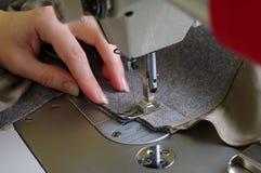Remet l'ouvrière couturière, le tissu et la machine à coudre, plan rapproché Photos stock