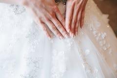 Remet la jeune mariée avec la manucure sur le fond de la robe blanche images libres de droits