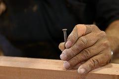 Remet le charpentier supérieur tenant le clou sur le morceau en bois avec l'espace de copie Photographie stock libre de droits