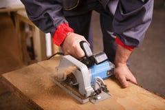 Remet le charpentier travaillant avec une scie circulaire photo stock
