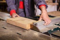 Remet le charpentier travaillant avec une scie circulaire Photos stock