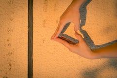 Remet le coeur dans la lumière de coucher du soleil Photographie stock libre de droits