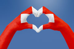 Remet le drapeau de la Suisse, forme un coeur Concept de symbole de pays, sur le ciel bleu Photographie stock libre de droits