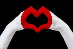 Remet le drapeau du Japon, forme un coeur Concept de symbole de pays, d'isolement sur le noir Photographie stock libre de droits